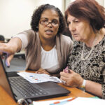 COMPUTER CLASS: Instructor Betty Tavares, left, gives a helping hand to student Lily Minaeliam during an adult digital-literacy workshop at Providence Public Library.