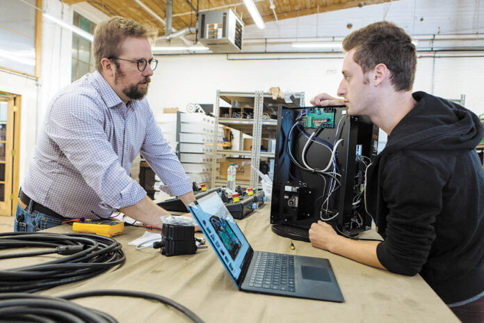 SETTING THE STAGE: Gareth Conner, left, founder and president of Creative Conners Inc., talks with automation technician Josh Stoller about a product Stoller is working on. It's a Spotline Practical hoist used in theatrical shows.    PBN PHOTO/RUPERT WHITELEY