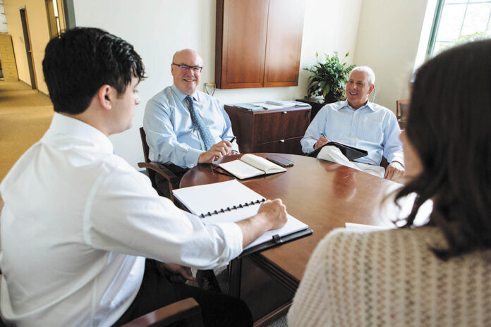 LENDING A HAND: Staff members at Rhode Island Infrastructure Bank gather to discuss agency business. From left is Business Development Analyst Graeme Ownjazayeri, CEO and Executive Director Jeffrey Diehl, Chief Operating Officer David Birkins and Senior Business Development Analyst Sydney Usatine.
