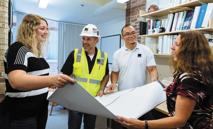 ACCORDING TO PLAN: From left, Assistant Project Manager Taylor Huntly, Superintendent Marty Mendonca, Senior Project Manager Chi Yik and Manager of Project Administration Sharon Barbary unfurl blueprints in the Providence office of Shawmut Design and Construction.PBN PHOTO/RUPERT WHITELEY
