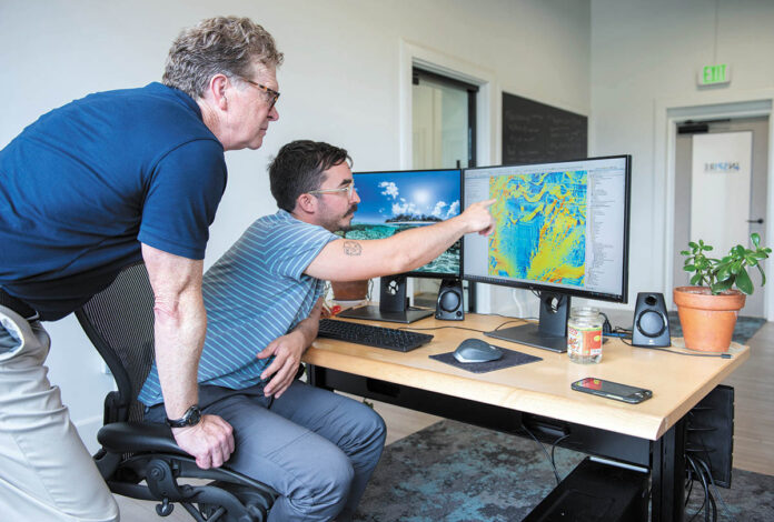 FLOOR PLANS: INSPIRE Environmental CEO Drew Carey, left, talks with Ben Taylor, a geographic information system specialist, at their Newport office. The company gathers imagery and data about the seafloor. Taylor creates visual representations of that information.