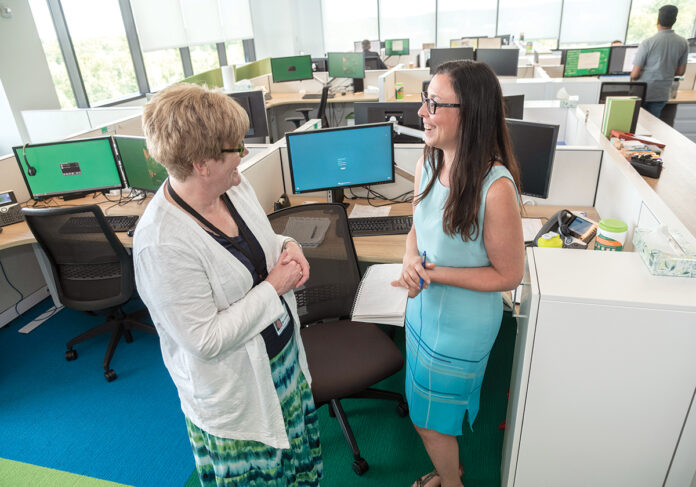 REIMAGINING WORK: The Citizens Financial Group campus in Johnston just passed its one-year anniversary, and its design and amenities have increased worker interaction, says the company. Plenty of windows lighten the mood for Louise Corrigan, left, vice president of lease administration, and Melissa Abatiello, portfolio specialist. / PBN PHOTO/MICHAEL SALERNO
