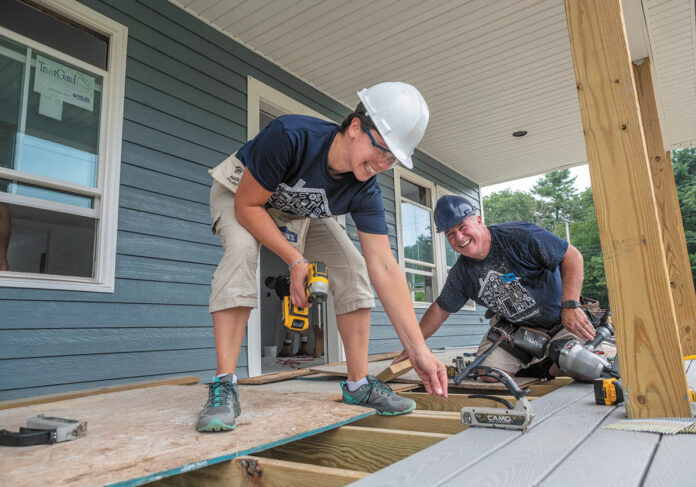 PITCHING IN: MetLife employees Haley Cuddy, left, senior marketing research consultant, and Tim Bowen, assistant vice president, claims, work on a new house in Exeter for a project overseen by South County Habitat for Humanity. / PBN PHOTO/MICHAEL SALERNO