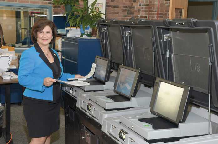 WHERE IT COUNTS: Secretary of State Nellie M. Gorbea, with the state's ballot-counting machines. A task force is investigating whether the election system needs an upgrade to reduce its vulnerability to hackers. / PBN PHOTO/MIKE SKORSKI
