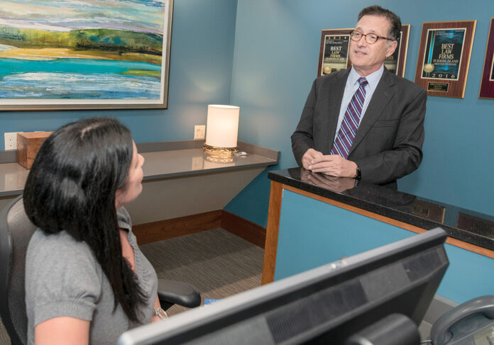 LEGAL EAGLE: James A. Ruggieri, managing partner at Higgins, Cavanaugh & Cooney, speaks with assistant Lisa Hennessey at the law firm's Providence office. / PBN PHOTO/ MICHAEL SALERNO