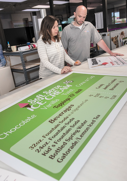 FINE PRINT: Karen Martins, left, franchise owner of FastSigns in Seekonk, inspects some placards with production/project installation manager Eric Dallaire. / PBN PHOTO/MICHAEL SALERNO