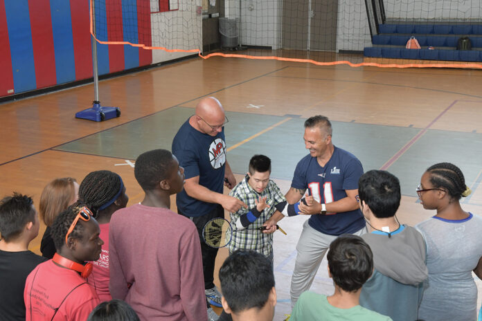 INTEGRATED CLASS: Coach Paul Rao, left, and coach Michael Diorio, right, work with students in an integrated physical education class at Mount Pleasant High School in Providence.    / PBN PHOTO/MIKE SKORSKI