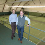 """COURTING MEMBERS: Lance Pryor, left, owner and member of Agawam Hunt's management team, and Joshua Helm, assistant general manager and controller, are pictured at the club's indoor tennis courts. Pryor said golf """"as the sole value proposition"""" is a challenging one right now. / PBN PHOTO/MIKE SKORSKI"""