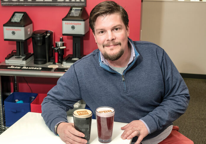 WRITTEN IN FROTH: Jeb Barnes, head of sales and operations at Ripples U.S. in North Kingstown, displays a beverage with a custom-made design in the foam, made by a Ripple Maker machine behind him. / PBN PHOTO/MICHAEL SALERNO