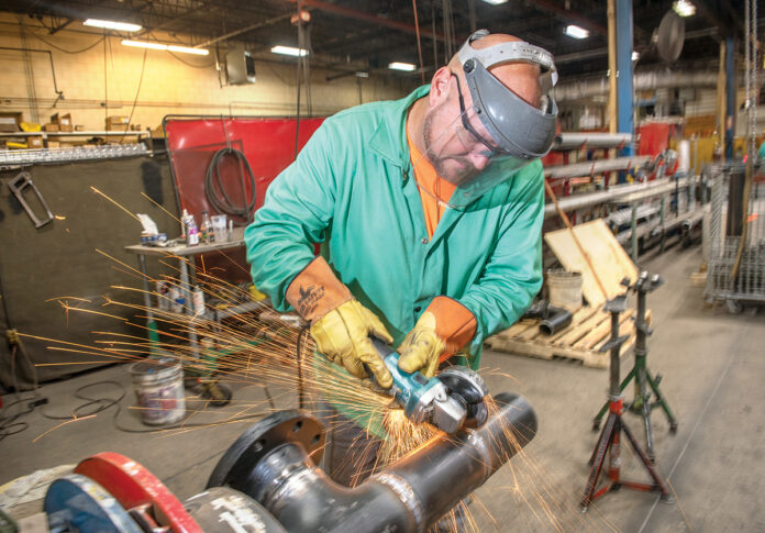 Thanks to digital imaging, more work for construction projects can be done in house. In this case Arden Building pipefitter/welder Andy Guimond can weld and grind 30 of the 40 connections needed for this pipe at the company's Pawtucket facility before taking the piece to the building site. / PBN PHOTO/DAVE HANSEN