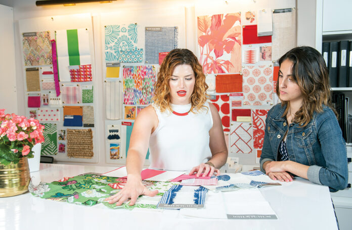 BUILDING A CAREER BY HAND: Rebecca Slater, left, design project director at Blakely Interior Design in North Kingstown, helps Brianna Chace, a New England Tech interior design major and intern at Blakely.  / PBN PHOTO/DAVE HANSEN
