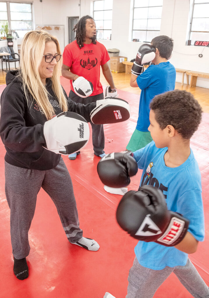 KID GLOVES: Team Rockstar Sports co-owners Rose Molina, front left, and Luis Feliz, back left, work at their gym with Christian Perriera, front, and Brody Henrique. / PBN PHOTO/MICHAEL SALERNO