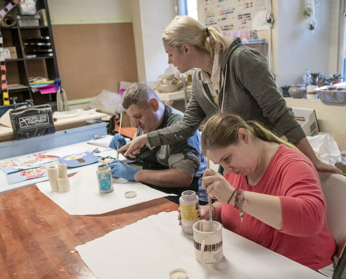ARTISTS AT WORK: Anna Thompson, standing, studio arts coordinator at The Groden Network, helps Bobby Brillon, left, and Jessica Vallee, students in Groden's adult program, with their pottery projects that will be sold at the organization's Pop-Up Shop from Black Friday through Christmas Eve. / PBN PHOTO/MICHAEL SALERNO