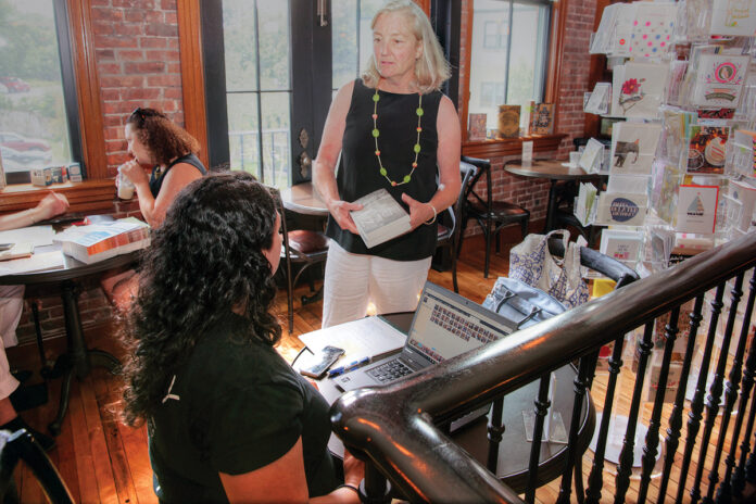 BUY LOCAL: Annie Philbrick, standing, owner of Savoy Bookshop & Café in Westerly, visits with customers in 2017. The shop is one of many Rhode Island businesses hoping shoppers buy local this holiday season. / PBN FILE PHOTO/BRIAN MCDONALD