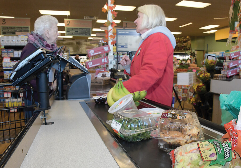 FRIENDLY FACE: Tom's Market in Tiverton saw increased sales in the months after an April strike at Stop & Shop. Cashier Elizabeth Pence, right, speaks with a customer. / PBN FILE PHOTO/MIKE SKORSKI