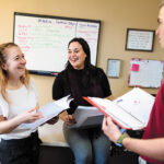 HEALTHY SMILES: From left, Jamie Oriol, field support coordinator; Samantha Bowen, director of communications and intern Austin Prario discuss their tasks at the American Heart Association of Southern New England in Providence. / PBN PHOTO/RUPERT WHITELEY
