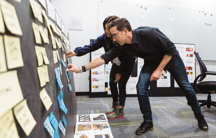 STEADY GROWTH: Richard Davia, managing director of creative and branding at (add)ventures, and Carli Kabilyo, assistant director of design and branding, add Post-it notes to a board at the company's new offices in East Providence. / PBN PHOTO/RUPERT WHITELEY