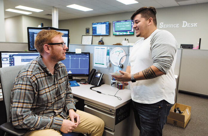 SHOP TALK: Vertikal6 service desk apprentices Steven Walsh, left, and Dylan Herrera share a conversation in the company's office. / PBN PHOTO/RUPERT WHITELEY