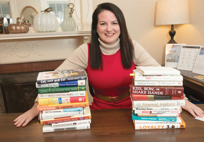 MORE AFFORDABILITY: Rhode Island Association of Realtors President Shannon Buss, bracketed by books that have been key to her real estate career, says three consecutive interest-rate cuts by the Fed haven't led to new homebuyers entering the market, but they have helped buyers who are already looking to afford more in a house. / PBN PHOTO/MICHAEL SALERNO