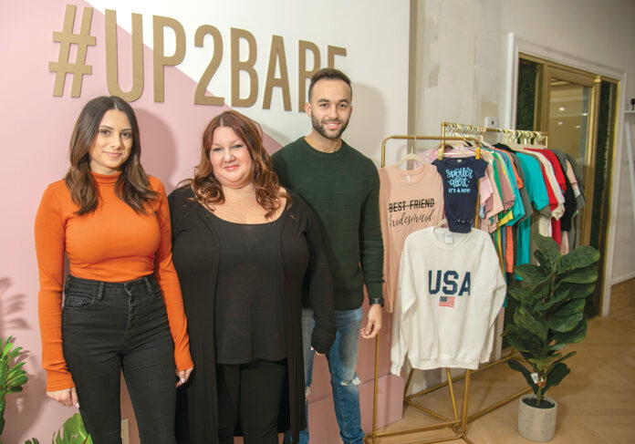 STITCHING SUCCESS: Heather Fortes, center, and her two business partners, Nicole Almeida, and Fortes' son, Nathan, have moved an online business in specialty clothing and accessories into a retail store in East Providence. / PBN PHOTO/MICHAEL SALERNO
