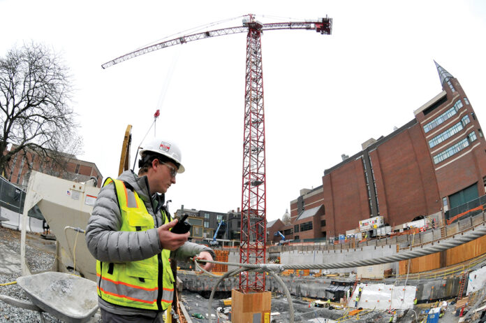 AIMING HIGH: A worker from Shawmut Design and Construction communicates with colleagues at the site of the new Brown University Performing Arts Center on College Hill in Providence. The tower crane is being used in the construction of the building, which is being overseen by Shawmut. / PBN PHOTO/MIKE SKORSKI