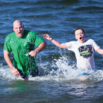 BRAVING BRISK TEMPS: Two participants in the 2019 Laid-back Fitness Frozen Clam Dip and Obstaplunge react to the temperature of the water in Narragansett Bay on New Year's Day. The 2020 plunge will take place Jan. 1 at Goddard Memorial State Park in East Greenwich. / COURTESY LAID-BACK FITNESS