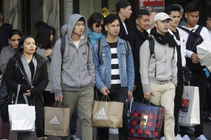 SHOPPERS CARRY bags as they cross a street in San Francisco on Nov. 29. More people turned to online shopping during one of the shortest holiday shopping seasons in years, helping boost total sales. Retail sales in the U.S. rose 3.4% between Nov. 1 and Dec. 24 from a year ago, according to early data from Mastercard SpendingPulse. That's down from last year, when total sales grew 5.1%. Online sales rose at a faster pace, up 18.8% from last year. / AP PHOTO/JEFF CHIU